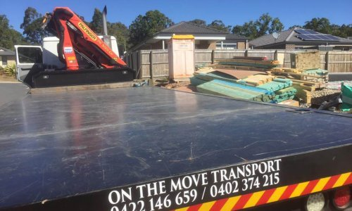 Crane truck finishing delivery of construction materials in Ormeau, Gold Coast