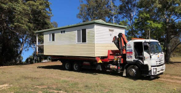 Tilt tray truck transporting a portable home on the Gold Coast